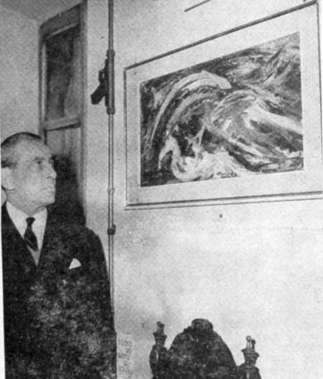 Ludovico Mares in front of one of his paintings at an exhibition